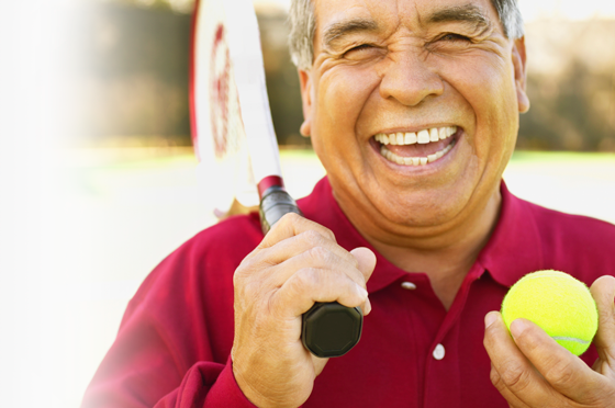 Laughing elderly latino man holding a tennis racket and tennis ball.